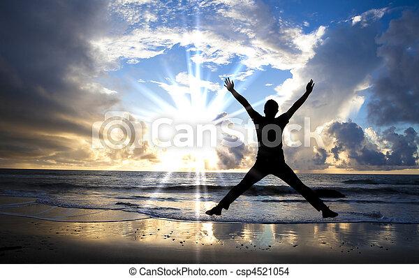 Šťastný muž skákající na pláži s krásným východem slunce - csp4521054