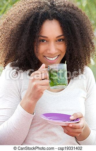 Mladá žena pije mentolový čaj - csp19331402