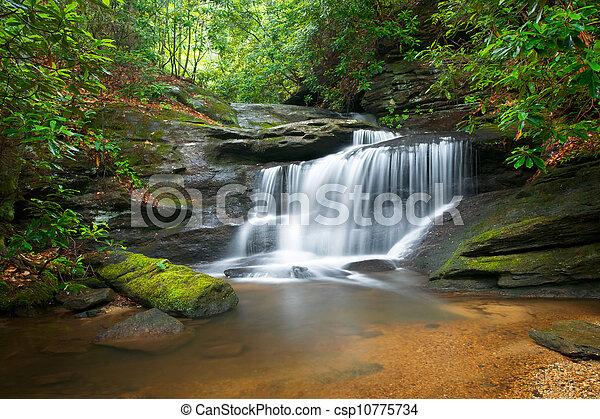 Rozsypané vodopády v modrém hřebenu s ledovými horami, s lunami zelenými stromy, stékajícími vodami - csp10775734